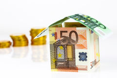 Casa y monedas euro de los billetes de banco Fotos de archivo libres de regalías