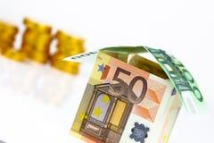 Casa y monedas euro de los billetes de banco Imagen de archivo