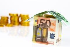 Casa y monedas euro de los billetes de banco Imagenes de archivo