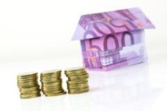 Casa y monedas euro de los billetes de banco Imagen de archivo libre de regalías