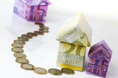 Casa y monedas euro de los billetes de banco Imágenes de archivo libres de regalías