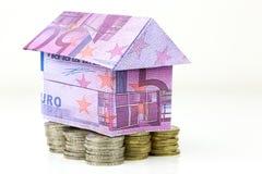 Casa y monedas euro de los billetes de banco Fotografía de archivo libre de regalías