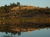 Casa y montaña reflejadas en agua Fotos de archivo
