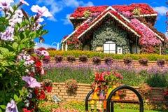 Casa y muñecas florales en el banco Imagen de archivo