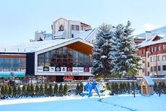 Casa y panorama de las montañas de la nieve en la estación de esquí búlgara Bansko Imagen de archivo