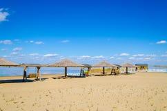 Casa y paraguas en la playa arenosa Foto de archivo