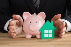 Casa y Piggybank de Protecting Green Paper del hombre de negocios Imagen de archivo libre de regalías