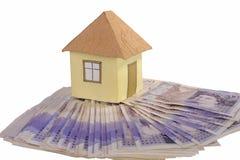 Casa y pila de dinero Imagen de archivo libre de regalías