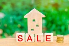 Casa y pila de madera de monedas con el ` de la venta del ` de la inscripción venta de la propiedad, hogar, propiedades inmobilia foto de archivo libre de regalías