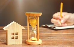 Casa y reloj de madera Una persona firma documentos Firma de un contrato para alquilar una casa o un apartamento Fabricaci?n de u fotografía de archivo
