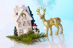 Casa y reno de la Navidad con las luces del bokeh Imágenes de archivo libres de regalías