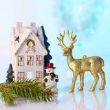 Casa y reno de la Navidad con las luces del bokeh Fotos de archivo