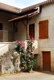 Casa y rosas de piedra francesas antiguas Fotos de archivo libres de regalías