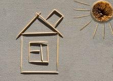 Casa y sol hechos de palillos en el hormigón imagen de archivo