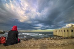 Casablanca 08-11-2016 A lonely Muslim woman sits on the edge of the sea on a stone wall staring at the threatening air that hangs. NCasablanca 08-11-2016nA Royalty Free Stock Photography