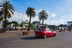 Casablanca Marocko - 11 Januari 2018: Röd taxi som passerar nära slott av rättvisa Arkivfoto