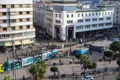 Top view of Casablanca square with clipped trees, tram and lots of people