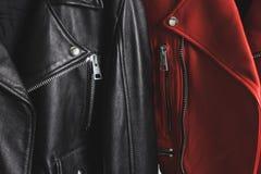 Casacos de cabedal vermelhos e pretos com zíper e os botões metálicos imagens de stock royalty free