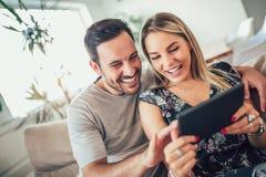Casal feliz atrativo que usa a tabuleta digital imagens de stock