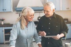 Casal idoso alegre que usa a tabuleta na cozinha imagens de stock royalty free