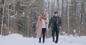 Casal novo no amor que andam na floresta do inverno um homem e um olhar da mulher em se que ri e que sorri dentro filme
