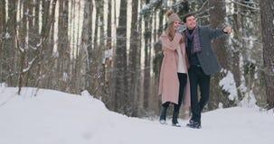 Casal novo no amor que andam na floresta do inverno um homem e um olhar da mulher em se que ri e que sorri dentro video estoque
