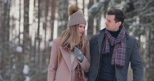 Casal novo no amor que andam na floresta do inverno um homem e um olhar da mulher em se que ri e que sorri dentro vídeos de arquivo