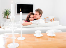 Casal novo que senta-se no sofá e na tevê de observação no hom Foto de Stock Royalty Free
