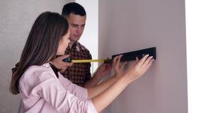 Casal positivo com fita métrica nas mãos que penduram a prateleira na parede após o reparo no apartamento video estoque