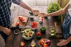 Casal que cozinha junto a salada dos vegetais do jantar na casa Fotografia de Stock