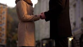 Casal que guarda as mãos maciamente, ainda no amor, caminhada romântica na cidade grande fotos de stock