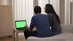 Casal que senta-se no sofá com um portátil que decide que comprar em linha em casa na sala de visitas vídeos de arquivo