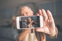 Casal superior alegre que fotografa-se no smartphone imagens de stock