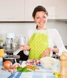 Casalinga che cucina carne con riso alla cucina fotografie stock libere da diritti