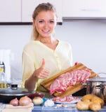 Casalinga che cucina con la carne fotografia stock