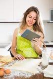 Casalinga che cucina con la compressa a casa Fotografie Stock