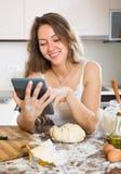 Casalinga che cucina con la compressa a casa Fotografia Stock