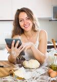 Casalinga che cucina con la compressa a casa Immagine Stock