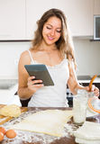 Casalinga che cucina con la compressa a casa Immagini Stock