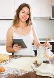 Casalinga che cucina con la compressa a casa Immagine Stock Libera da Diritti