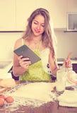 Casalinga che cucina con la compressa a casa Fotografia Stock Libera da Diritti