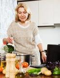 Casalinga che utilizza taccuino mentre cucinando nella cucina immagine stock