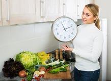 Casalinga con gli orologi alla cucina Fotografie Stock Libere da Diritti