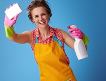 Casalinga con il detersivo di pulizia facendo uso della spugna della cucina sul blu fotografia stock