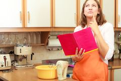 Casalinga con il libro di cucina in cucina Immagini Stock Libere da Diritti