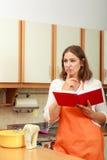 Casalinga con il libro di cucina in cucina Fotografia Stock Libera da Diritti