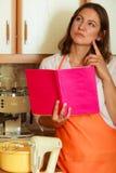 Casalinga con il libro di cucina in cucina Immagine Stock Libera da Diritti