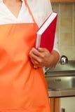 Casalinga con il libro di cucina in cucina Immagine Stock