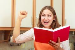 Casalinga con il libro di cucina in cucina Immagini Stock