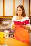 Casalinga con il libro di cucina in cucina Fotografia Stock